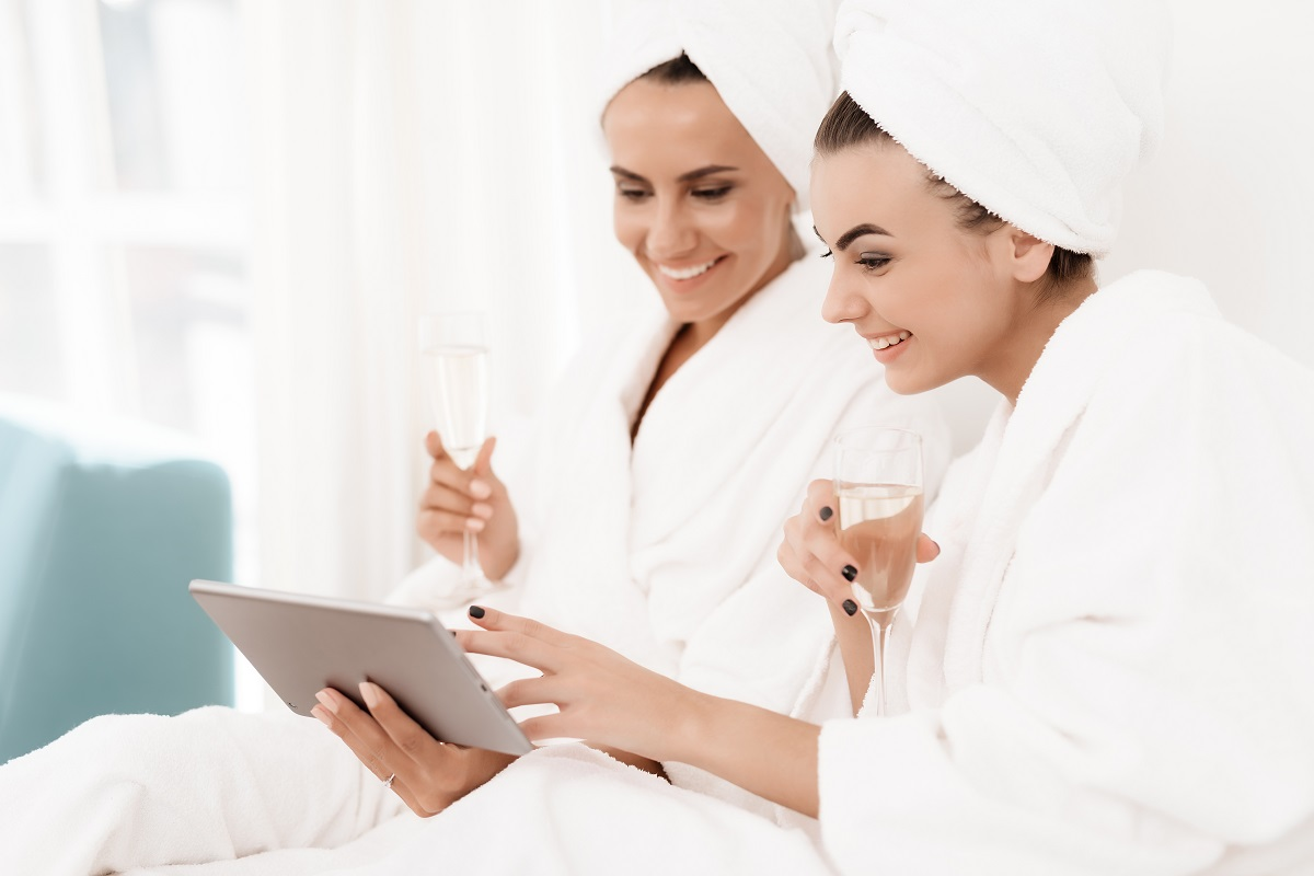 Brunettes in white bathrobes have fun in a bright room.