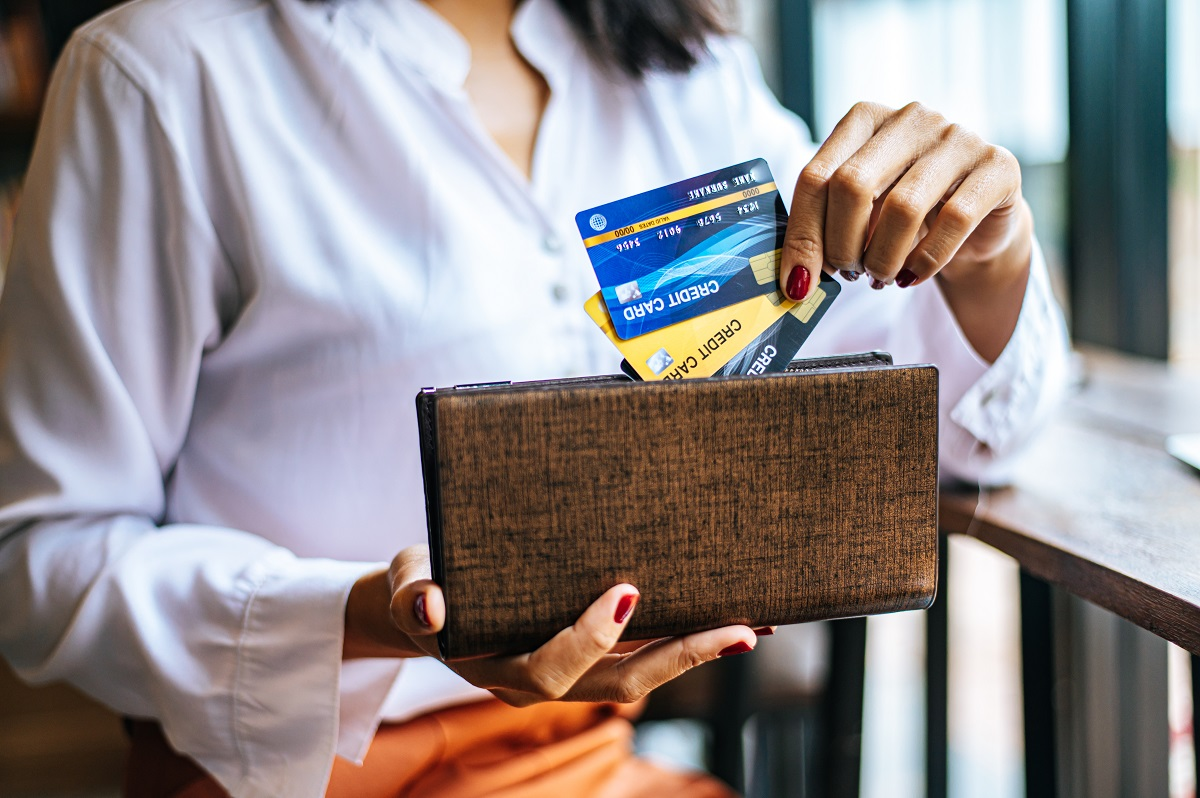 Accepting credit cards from a brown purse to pay for goods on co