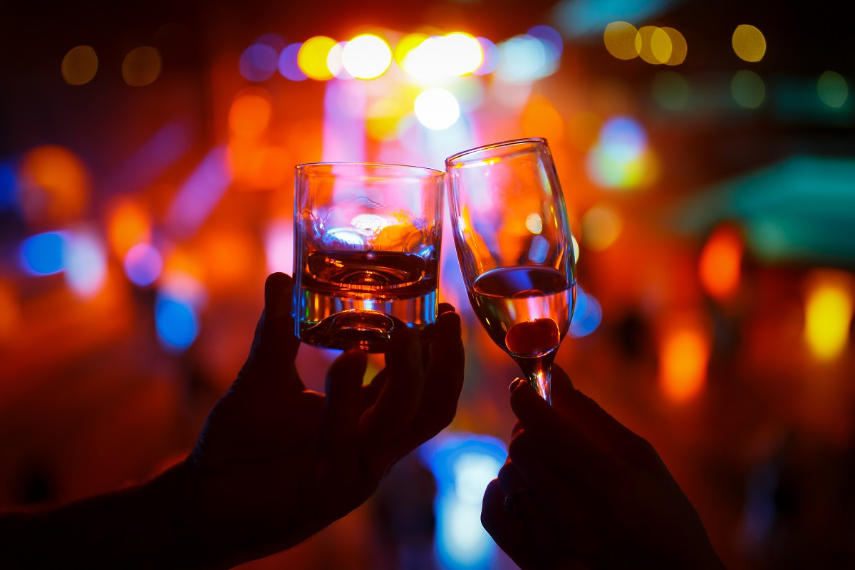 Wineglass of champagne in woman hand and a glass of whiskey in a man hand against a background of colored lights