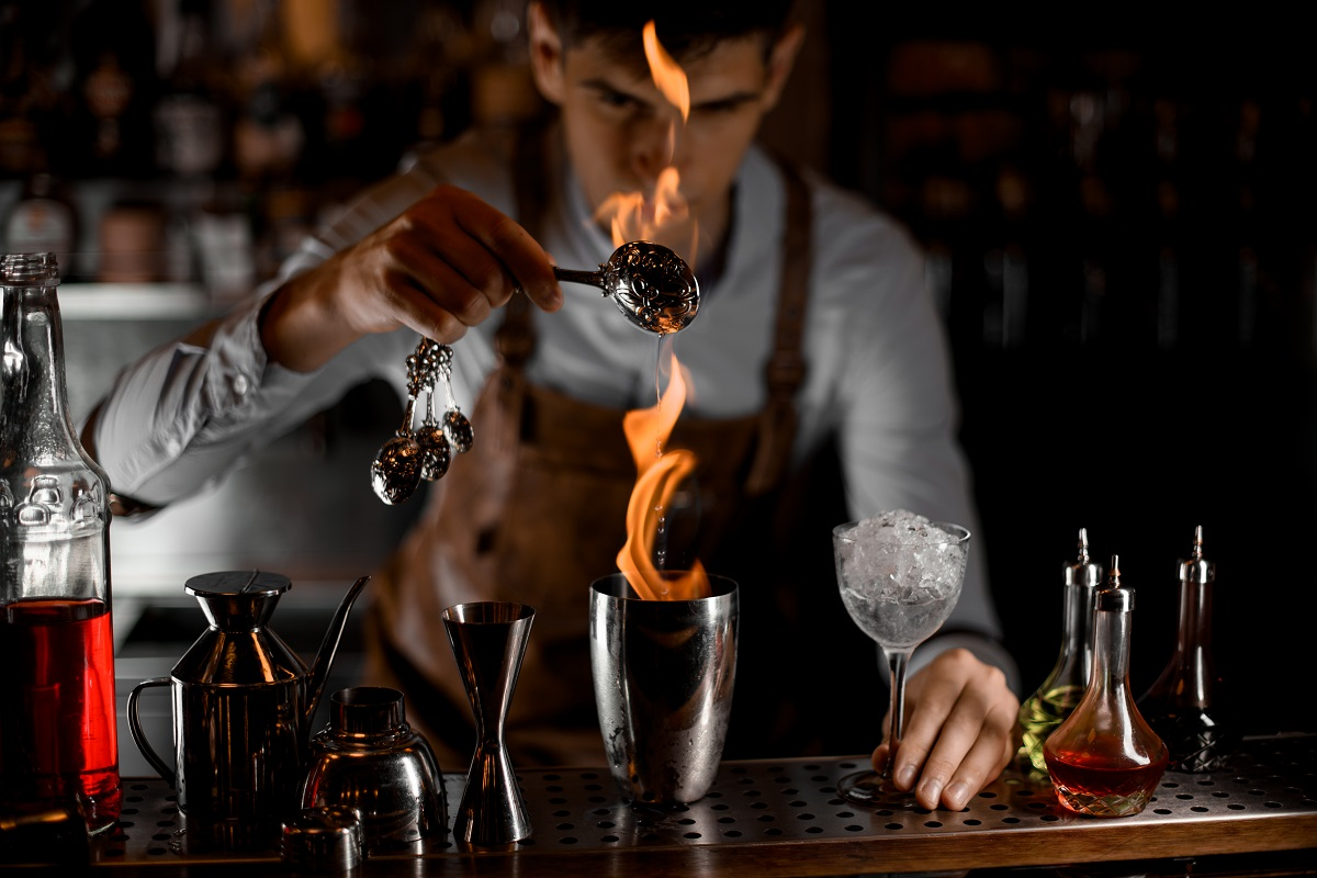 Attractive male bartender pouring an essence from the spoon in the flame to the steel shaker