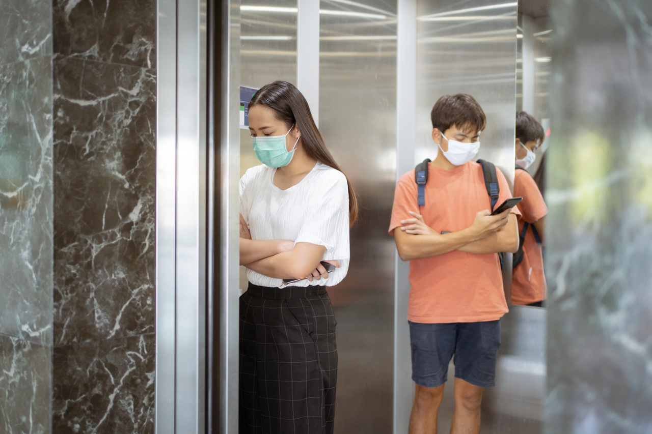 Two people practicing social distancing in an elevator