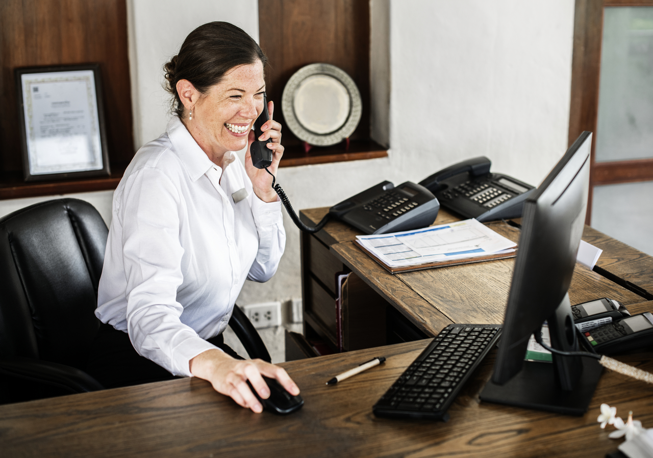 A female hotel receptionist on the phone